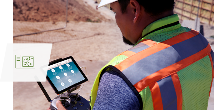 A man in a hard hat stands in a construction area, studying a menu on the screen of a drone remote piloting device.