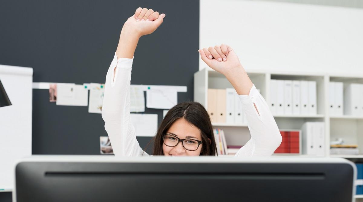 Umg kvinna vid dator gör segergest