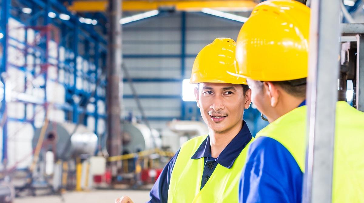 Två män i gul hjälm samtalar i industrilokal