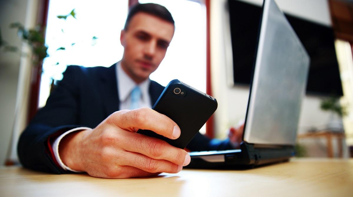 Affärsman använder bärbar dator och smartphone, smartphone i fokus