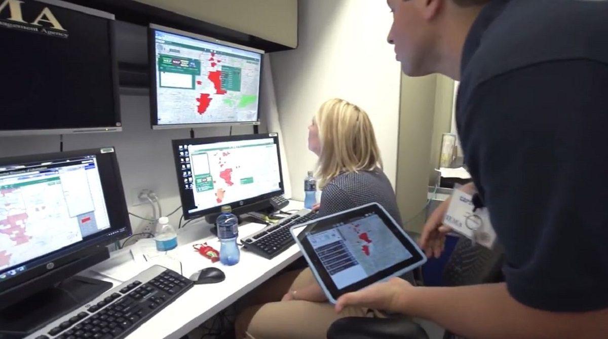 Man och kvinna i kontrollrum med skärmar som visar dashboards