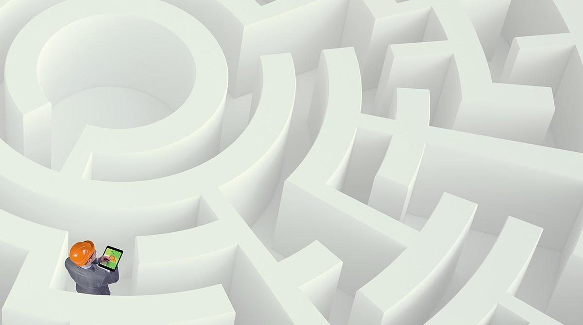 Man med hjälm och surfplatta i labyrint