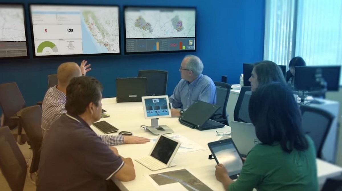Människor i sammanträde tittar på dashboards med kartvisualiseringar