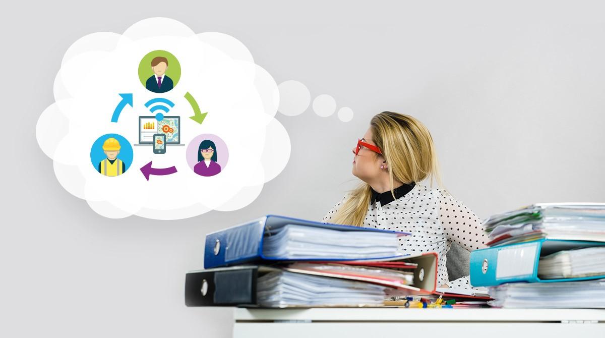 Ung kvinna vid skrivbord belamrat av pärmar drömmer om digitalt arbetsflöde