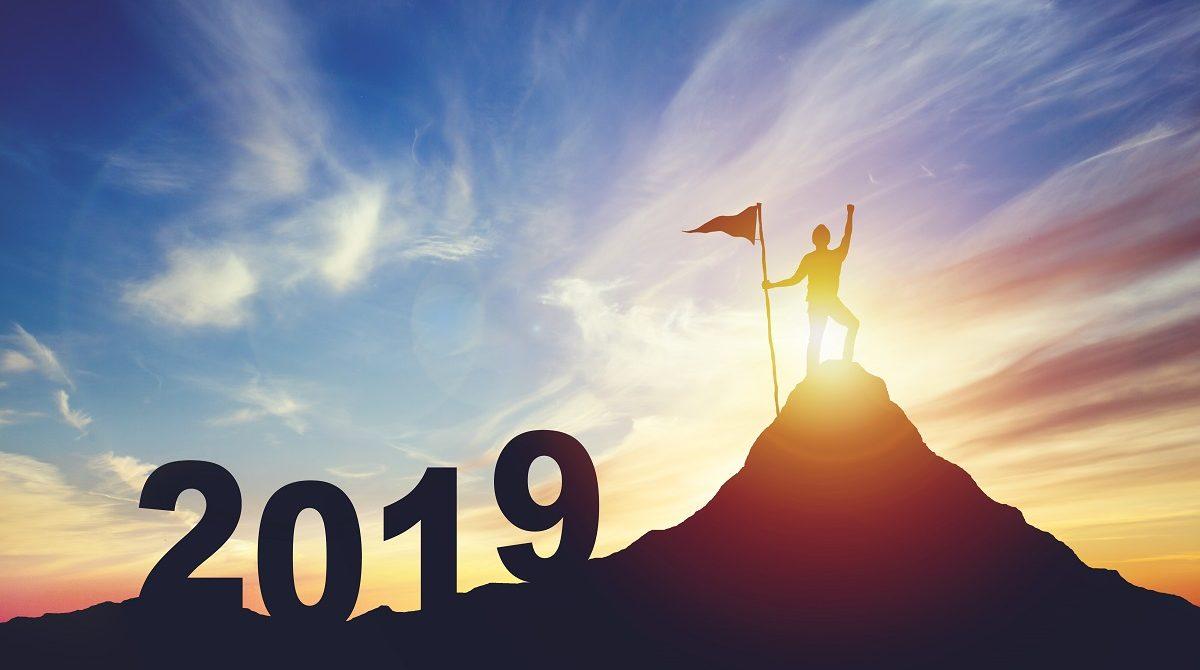 Siluett med årtalet 2019 och man med flagg på bergstopp