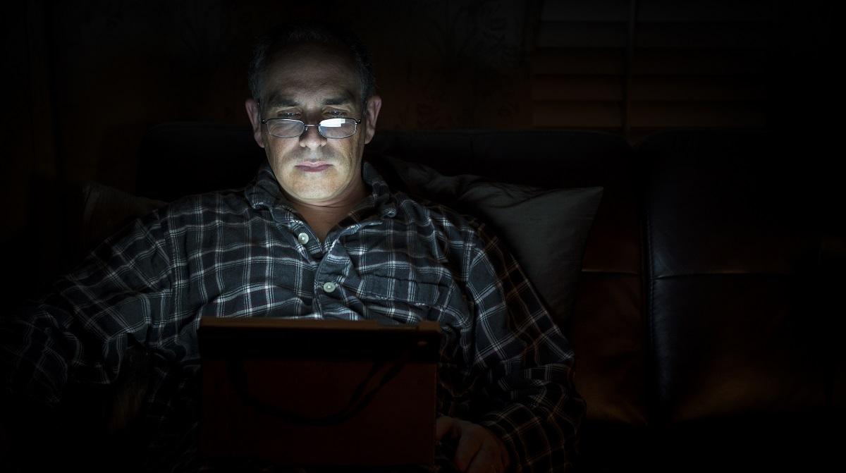 Sömlös man i skenet av datorskärm