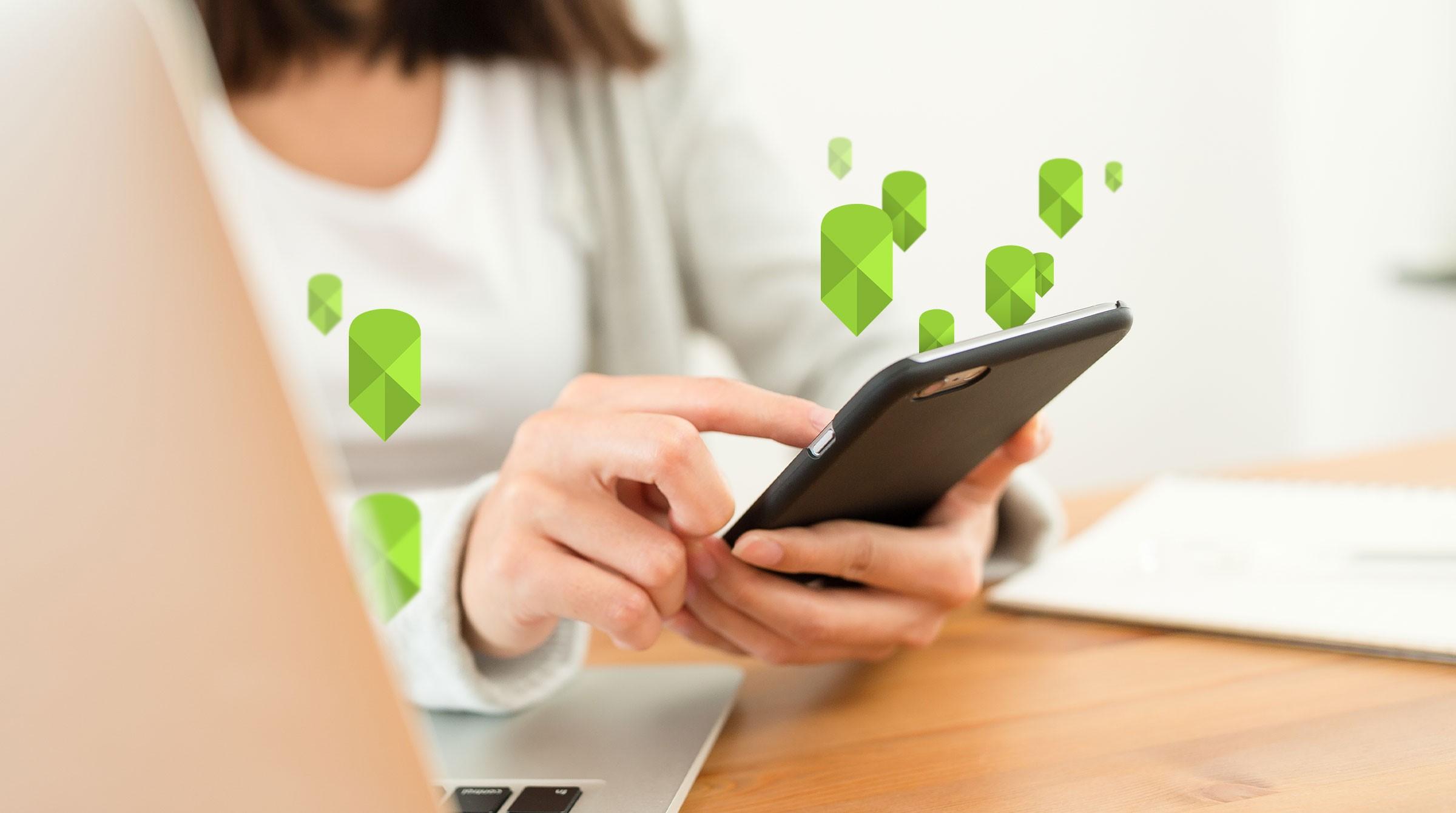 Kvinna, dator, smartphone och platsmarkörer
