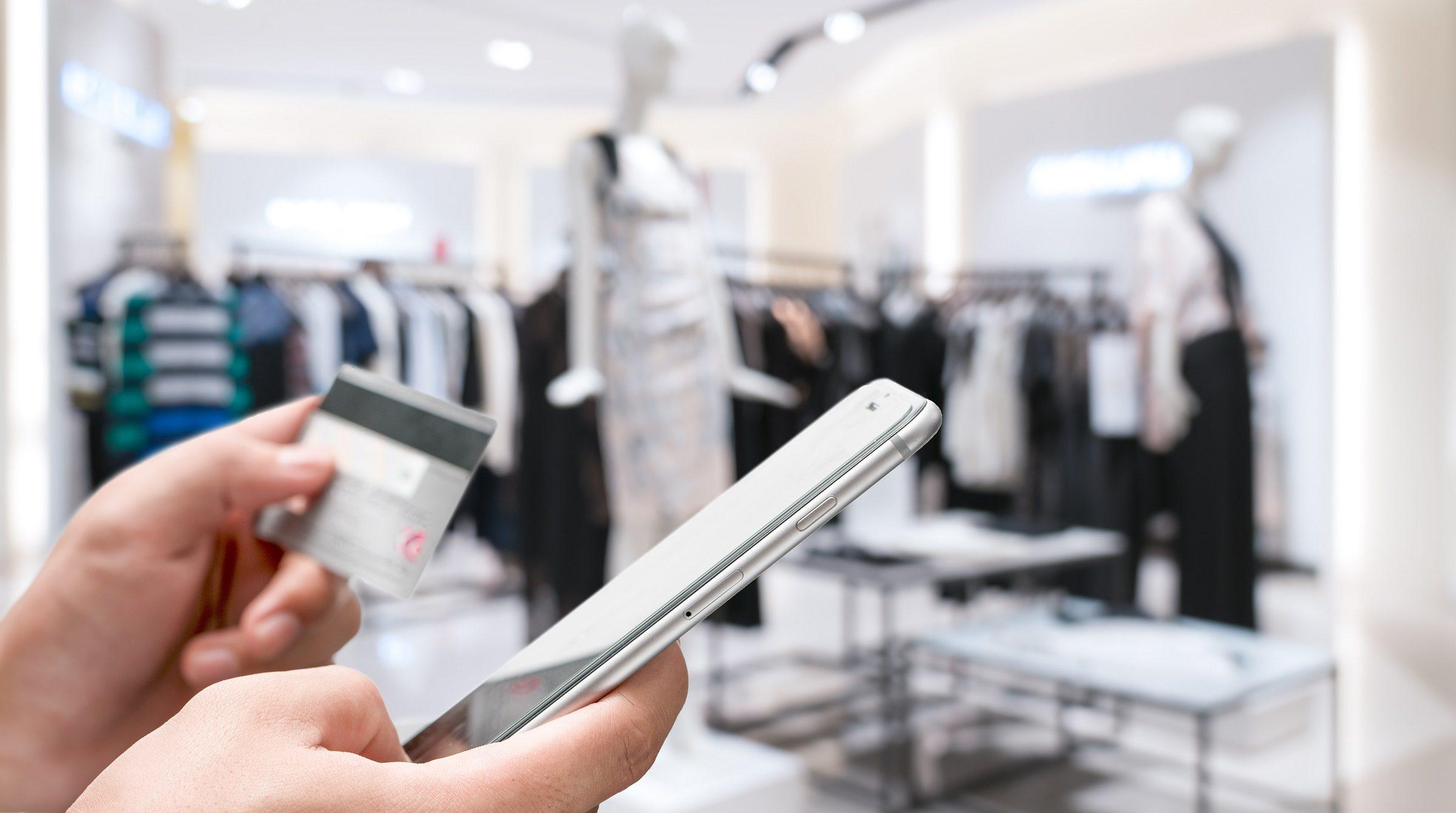 Hand med kreditkort och smartphone i butik