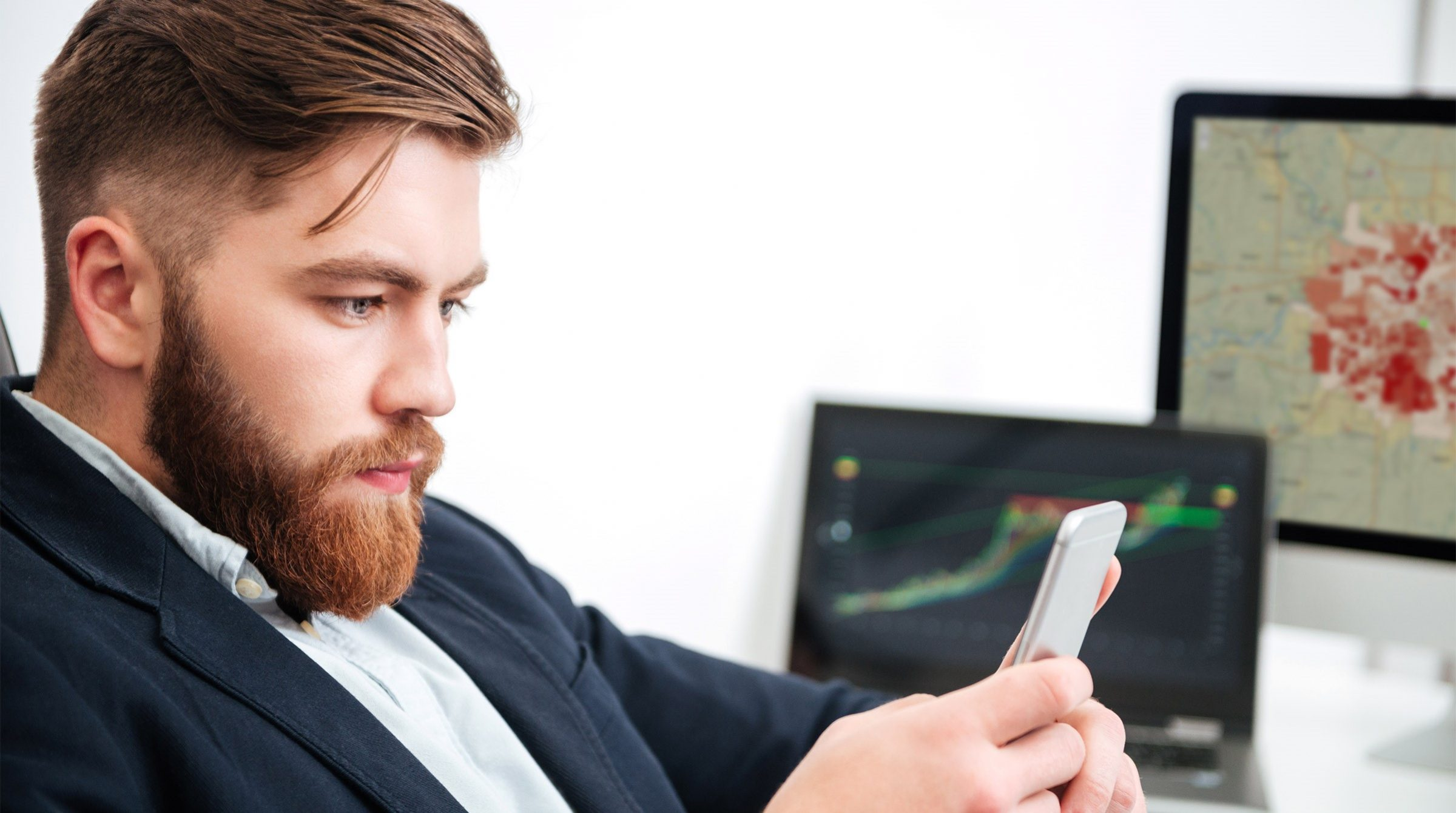 Digital kund med smartphone och två dataskärmar i bakgrunden