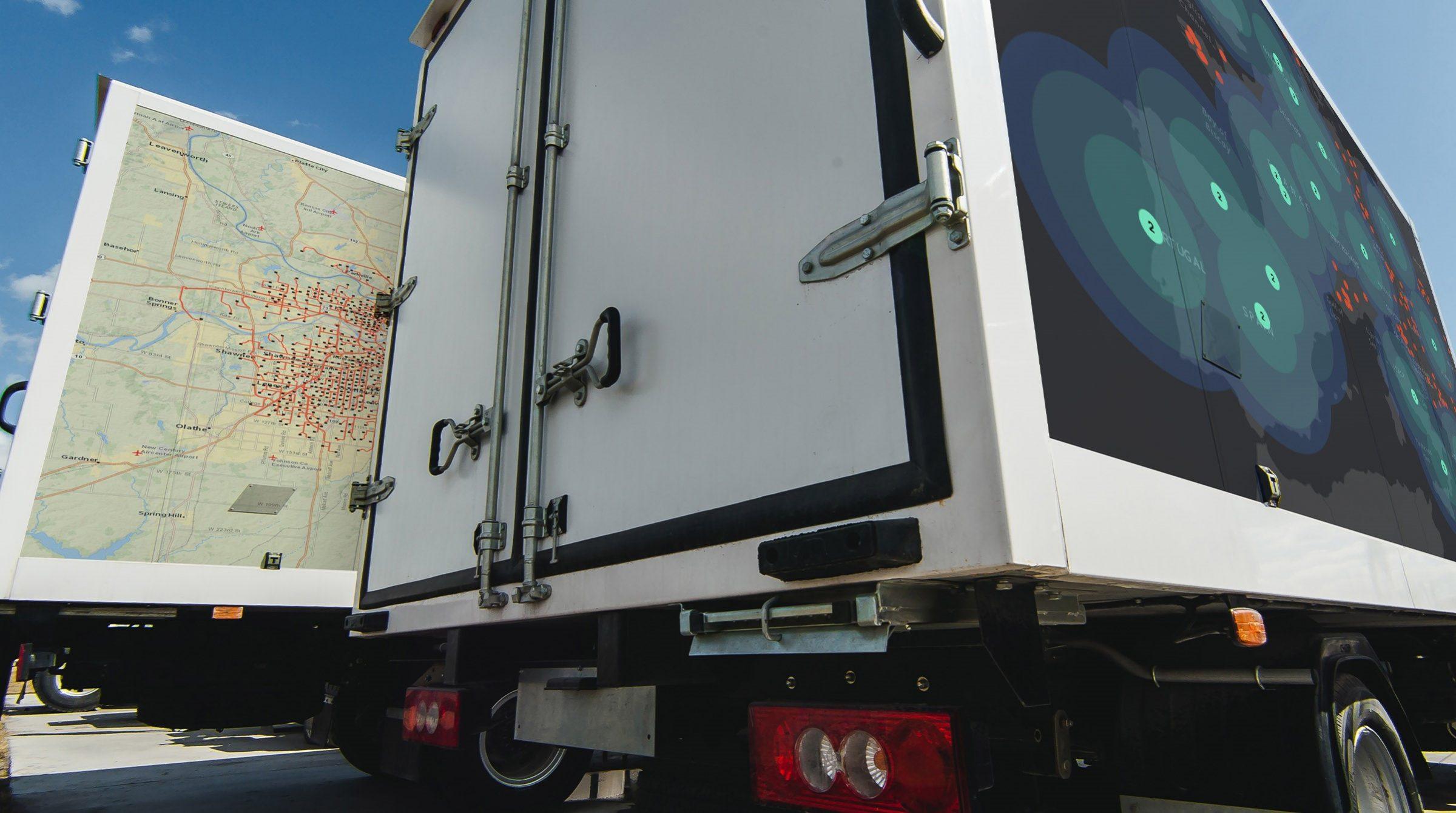 Lastbilar stripade med visualiseringar av data på kartor