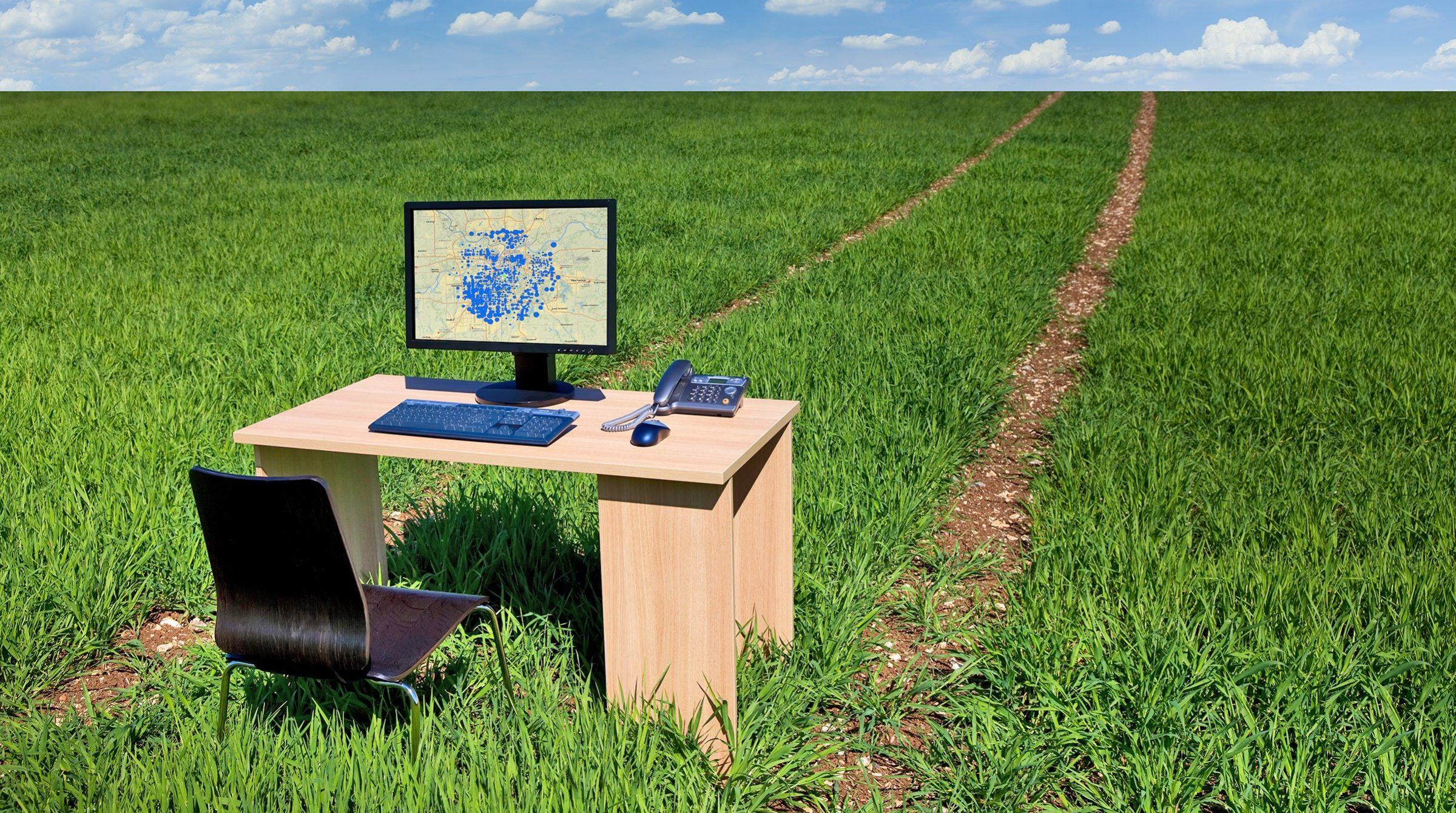 Fält med hjulspår och skrivbord med dataskärm som visar karta