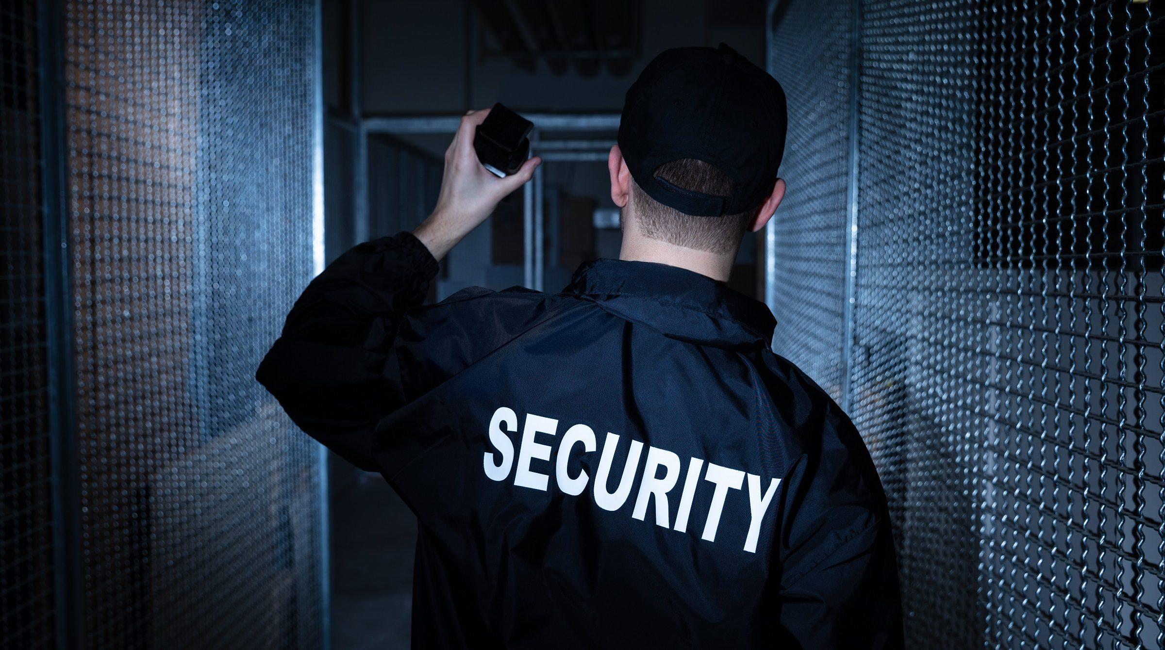 Säkerhetsvakt lyser med ficklampa i lagerlokal