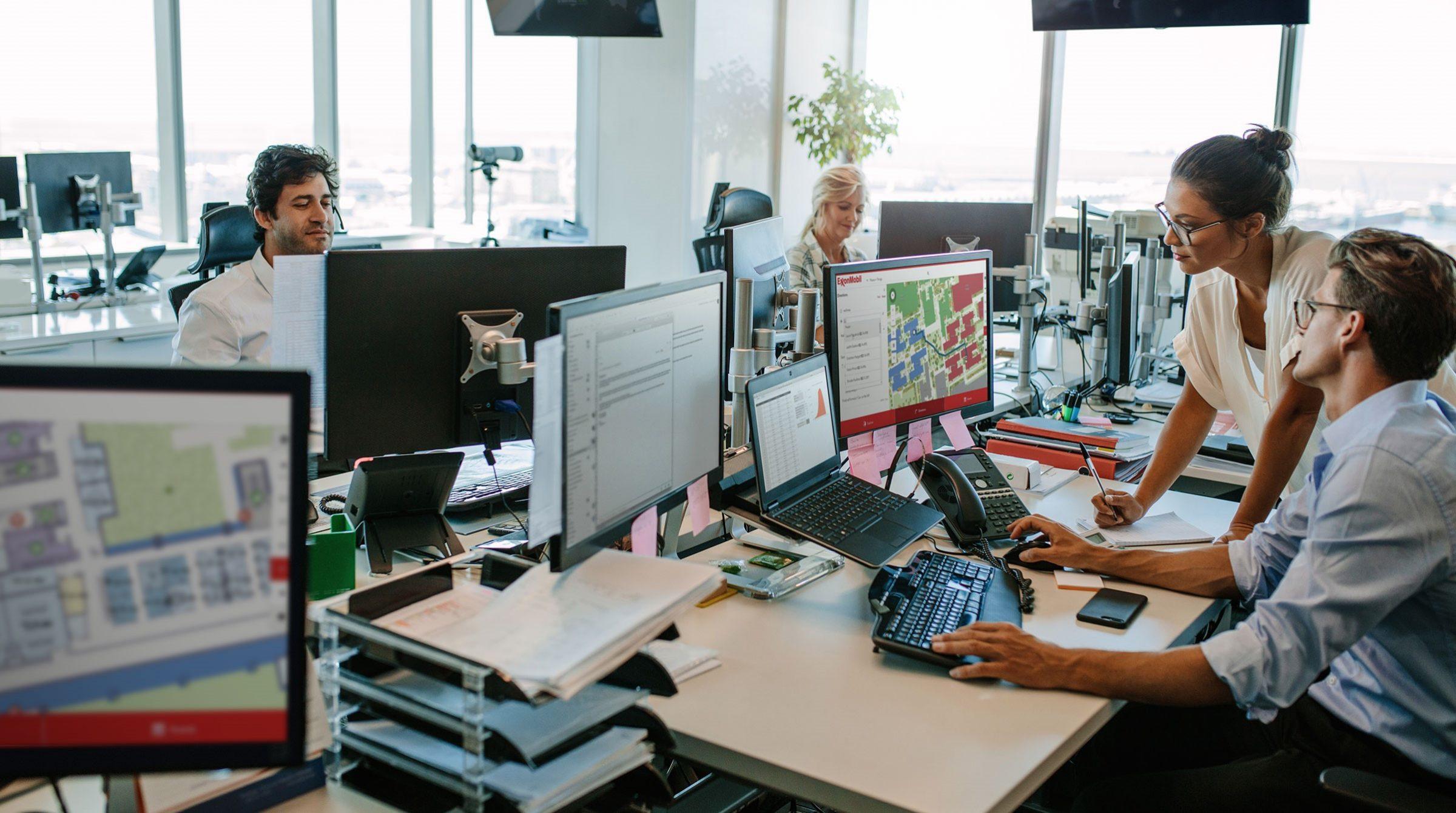 Kontorslandskap med datorer med kartverktyg