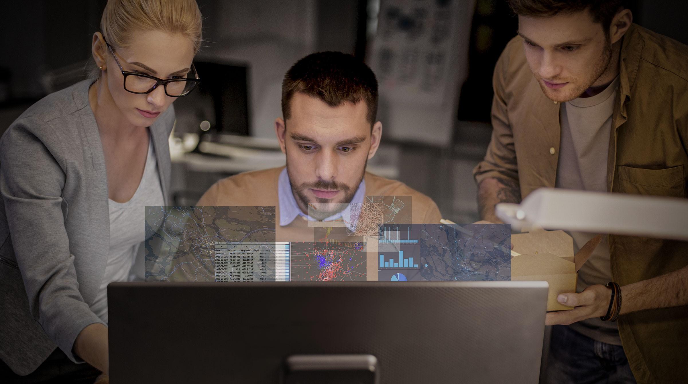 Tre unga tjänstemän tittar på en dataskärm