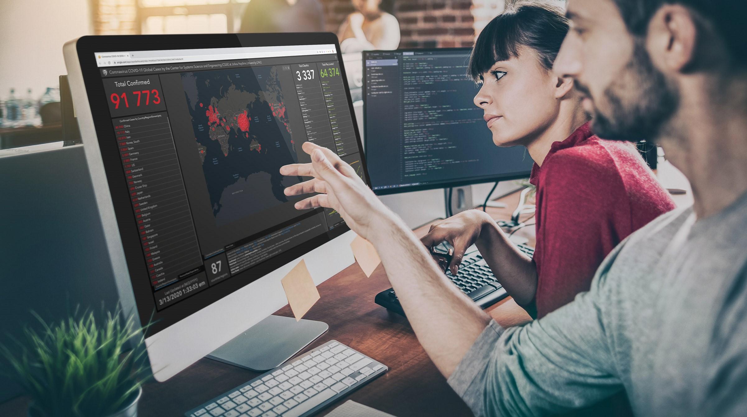 Tjänstemän vid dator tittar på Corona dashboard