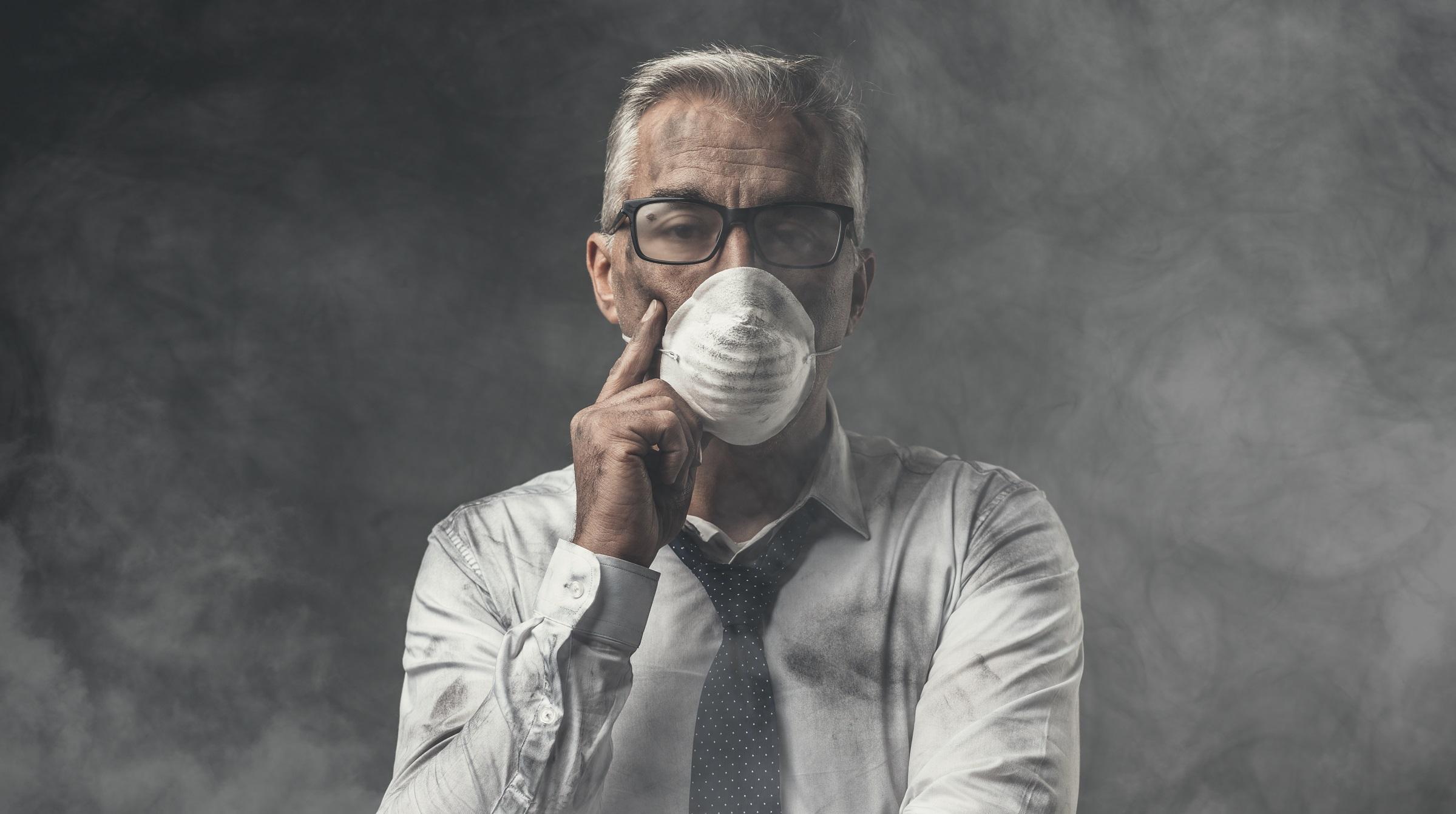 Affärsman i ansiktsmask står i moln av luftförorening