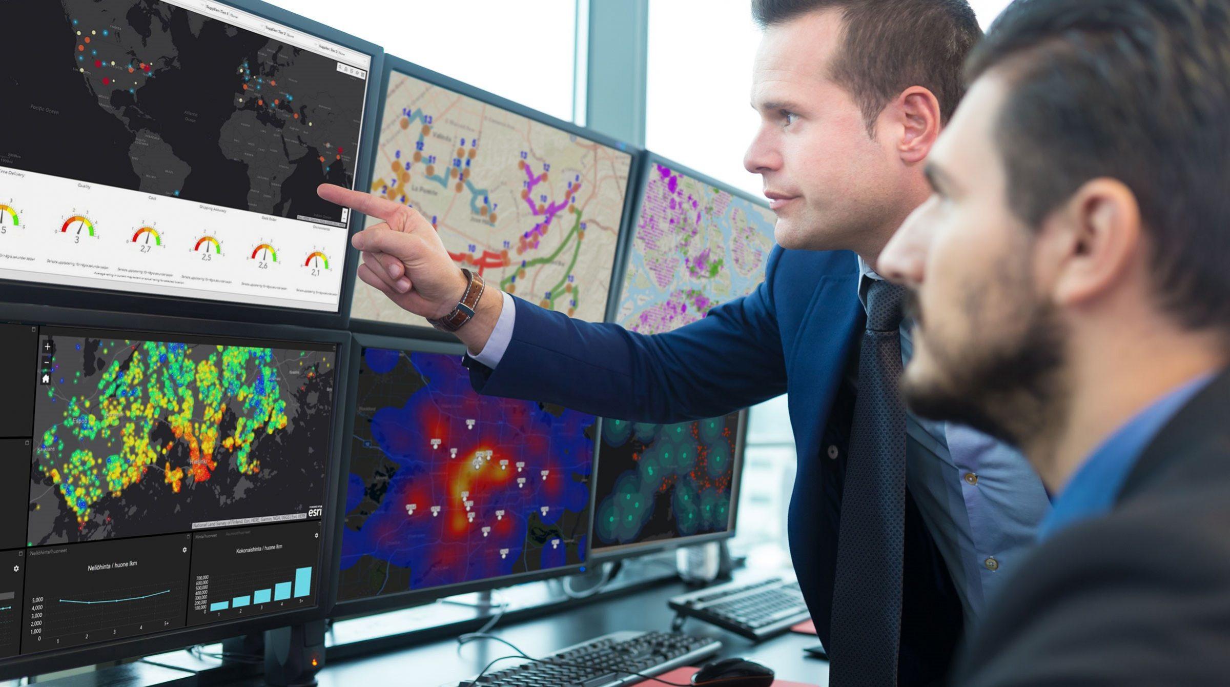 Affärsmän i kontrollrum framför skärmar med kartvisualiseringar
